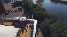 Quadrocopter sorvola il ristorante dell'estate con la tenda bianca sul tetto di vecchia costruzione al fiume La gente video d archivio