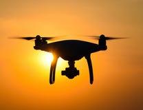 Quadrocopterssilhouet tegen de achtergrond van de zonsondergang Royalty-vrije Stock Afbeelding