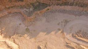 Quadrocoptervliegen over de donkergele kloof Een pianist speelt op een witte piano op geel zand Mening van hierboven stock videobeelden