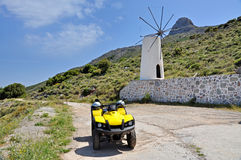 Quadrocycle and windmill. On the mountain Royalty Free Stock Photo