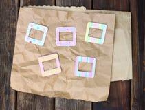 Quadros coloridos da foto no papel amarrotado no fundo de madeira Fotos de Stock Royalty Free