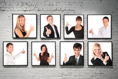 Quadros com os povos aprovados do gesto na parede de tijolo branca Fotos de Stock