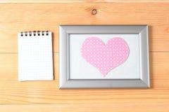 Quadros da foto, cartão vazio e corações feitos a mão sobre o fundo de madeira Fotografia de Stock