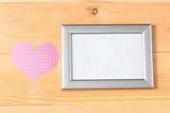 Quadros da foto e corações feitos a mão sobre o fundo de madeira Fotos de Stock