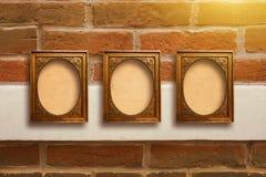 Quadros de madeira dourados para imagens na parede de tijolo velha Foto de Stock
