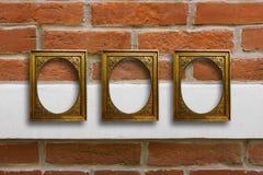 Quadros de madeira dourados para imagens na parede de tijolo velha Imagens de Stock Royalty Free