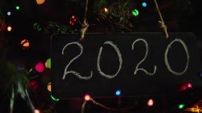 2020 quadros de rotulação que penduram em um ramo são árvore de Natal