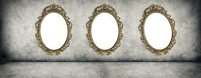 Quadros dourados ornamentado que penduram no muro de cimento Imagens de Stock