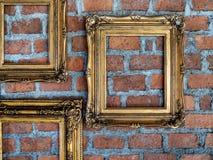 Quadros dourados ornamentados velhos vazios que penduram na parede de tijolo imagens de stock