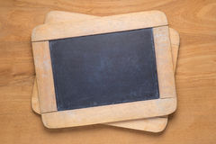 Quadros-negros pequenos na tabela de madeira Imagem de Stock