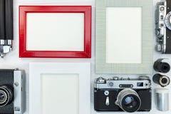 Quadros vazios da foto e câmeras retros no fundo de madeira branco Fotografia de Stock