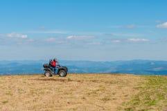 Quadruple faisant du vélo dans les montagnes Conducteur équipé d'ATV photographie stock