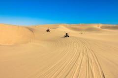 Quadruplez conduire les personnes - deux cyclistes heureux dans le désert de sable Photos stock