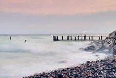 Quai en bois abandonné en mer dans le lever de soleil La couleur rose bleue douce du ciel, tache floue ondule Image libre de droits