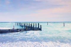 Quai en bois abandonné en mer dans le lever de soleil La couleur rose bleue douce du ciel, tache floue ondule Photographie stock libre de droits
