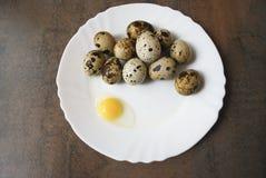 Quailägg på en vit pläterar Ett ägg är brutet Royaltyfri Bild