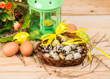 Quail and chicken eggs in a basket and a candlestick Stock Photography