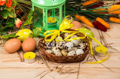 Quail and chicken eggs in a basket and a candlestick Royalty Free Stock Photography