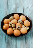 Quail and chicken eggs in a black bowl. Eggs in a black bowl on a turquoise vintage surface Royalty Free Stock Photo