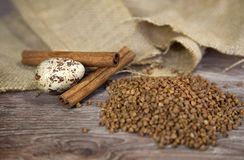 Quail egg with buckwheat and cinnamon. On wood background royalty free stock photo