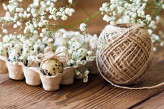 Quail egg is decorated with a bow of twine, baby`s breath flowers. Festive Easter decor. Royalty Free Stock Photos