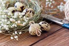 Quail egg is decorated with a bow of twine, baby`s breath flowers. Festive Easter decor. Royalty Free Stock Image