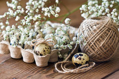 Quail egg is decorated with a bow of twine, baby`s breath flowers. Festive Easter decor. Stock Images