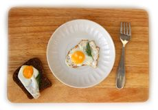 Quail egg on a saucer flat lay. Fried Quail egg on a white saucer and wholegrain bread flat lay on wooden board Royalty Free Stock Image