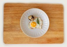 Quail egg on a saucer flat lay. Fried Quail egg on a white saucer flat lay on wooden board Royalty Free Stock Photography