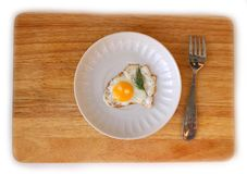 Quail egg on a saucer flat lay. Fried Quail egg on a white saucer flat lay on wooden board Stock Images