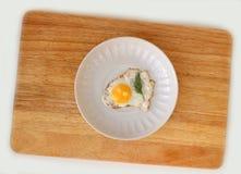 Quail egg on a saucer flat lay. Fried Quail egg on a white saucer flat lay on wooden board Stock Image