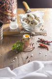 Quail egg arranged on wooden table with salt and pepper parsley sprig. Quail eggs arranged on wooden table with salt and pepper parsley sprig. One egg split open Royalty Free Stock Image