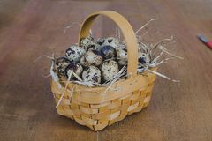 Quail eggs in bamboo basket On the old wood. Table background stock images