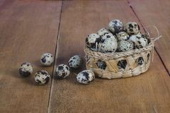 Quail eggs in bamboo basket On the old wood. Table background stock photos