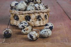 Quail eggs in bamboo basket On the old wood table. Background royalty free stock image