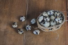 Quail eggs in bamboo basket On the old wood. Table background royalty free stock image