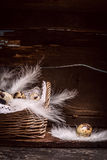 Quail eggs in basket with feathers  on old kitchen wooden table, over rustic background, side view Stock Photo