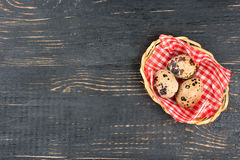 Quail eggs in basket. Fresh quail eggs in a basket on a dark wooden background Stock Images