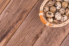 Quail eggs in a basket on old wooden table. Top view Royalty Free Stock Photos
