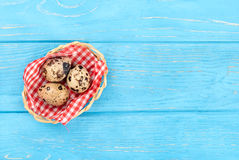 Quail eggs in basket. Three fresh quail eggs in a basket on an empty wooden background, top view Stock Photography