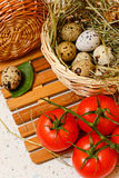 Quail eggs in basket. Tomato. Royalty Free Stock Photography
