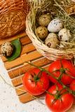 Quail eggs in basket. Tomato. Quail eggs in basket. A tomato Royalty Free Stock Photography