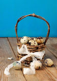 Quail eggs in a basket on a wooden table Royalty Free Stock Images