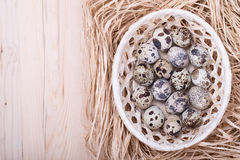 Quail eggs in a basket on wooden table Royalty Free Stock Images