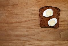 Quail eggs on a black bread on a broun wooden table. Top view Royalty Free Stock Images