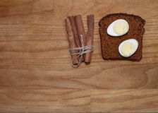 Quail eggs on a black bread and cinnamon stick on a broun wooden table. Top view Royalty Free Stock Photo