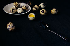 Quail eggs on a black textured background. Raw broken egg with the yolk. Easter card. Side view. Stock Images