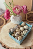 Quail eggs in a box and a bouquet of flowers Stock Photo