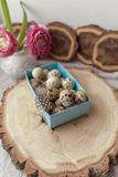 Quail eggs in a box and a bouquet of flowers Royalty Free Stock Photo