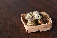 Quail eggs in a box on a rustic wooden background, top view, selective focus. Spotted quail eggs arranged in a box on a rustic wooden background, top view Royalty Free Stock Photography